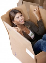 Pretty woman smiling inside a mystery box isolated during an Inside Magic photo shoot.